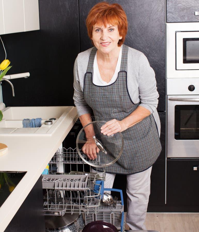 Γυναίκα που διπλώνει τα πιάτα στο πλυντήριο πιάτων στοκ φωτογραφίες