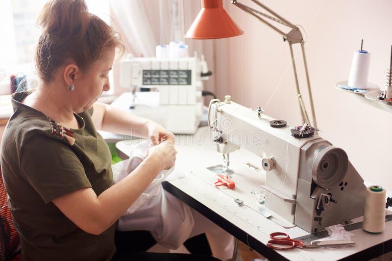 Γυναίκα που ράβει το άσπρο φόρεμα με τα χέρια και τη βελόνα Ράβοντας μηχανή, ψαλίδι, καρφίτσες, νήματα, επιτραπέζιος λαμπτήρας στ στοκ εικόνες