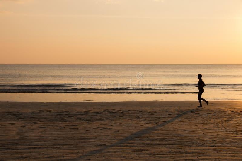 Γυναίκα που τρέχει στην παραλία στο ηλιοβασίλεμα, υγιής τρόπος ζωής στοκ εικόνες με δικαίωμα ελεύθερης χρήσης