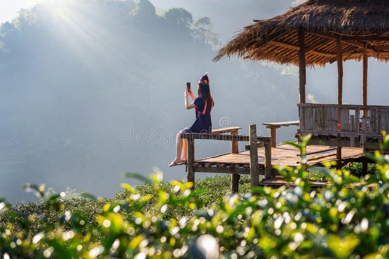 Γυναίκα που φορά τη συνεδρίαση φορεμάτων φυλών λόφων στην καλύβα στον πράσινο τομέα τσαγιού στοκ εικόνα