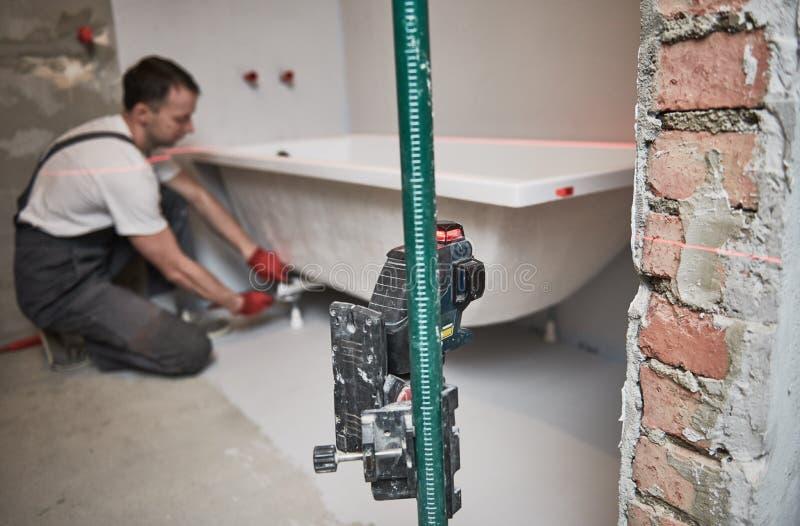 Εγκατάσταση Bathtube εγκαθιστώντας και τοποθετώντας λουτρό υδραυλικών με το επίπεδο λέιζερ στοκ εικόνες