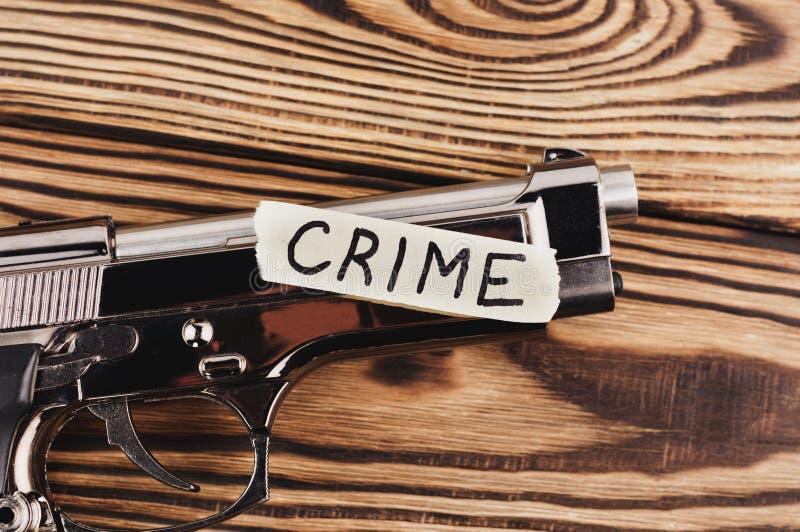 ΕΓΚΛΗΜΑ επιγραφής σε σχισμένο χαρτί και το στιλπνό πιστόλι στοκ φωτογραφίες