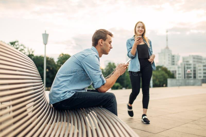 Εθισμένοι οι τηλέφωνο άνθρωποι δεν παρατηρούν ο ένας τον άλλον στοκ εικόνες