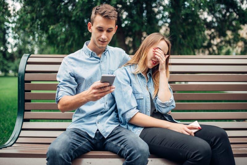 Εθισμένοι τηλέφωνο άνθρωποι, ζεύγος στον πάγκο στο πάρκο στοκ φωτογραφία με δικαίωμα ελεύθερης χρήσης