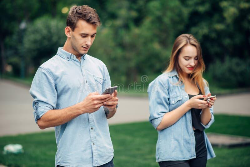 Εθισμένοι τηλέφωνο άνθρωποι, ζεύγος στο θερινό πάρκο στοκ εικόνες