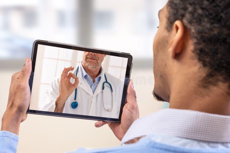 Εικονική ζωντανή συνομιλία με τον ασθενή με την ψηφιακή ταμπλέτα και έναν γιατρό μέσω Διαδικτύου -εγχώρια προσοχή για έναν νέο αρ στοκ εικόνες