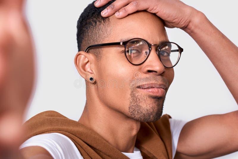 Εικόνα κινηματογραφήσεων σε πρώτο πλάνο του όμορφου νεαρού άνδρα αφροαμερικάνων που χαμογελά, που φορά eyewear, που εξετάζει τη κ στοκ φωτογραφία