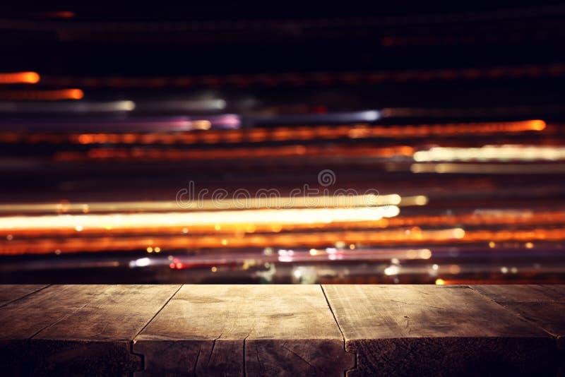 Εικόνα του ξύλινου πίνακα μπροστά από θολωμένο το περίληψη υπόβαθρο φω'των εστιατορίων στοκ φωτογραφία με δικαίωμα ελεύθερης χρήσης