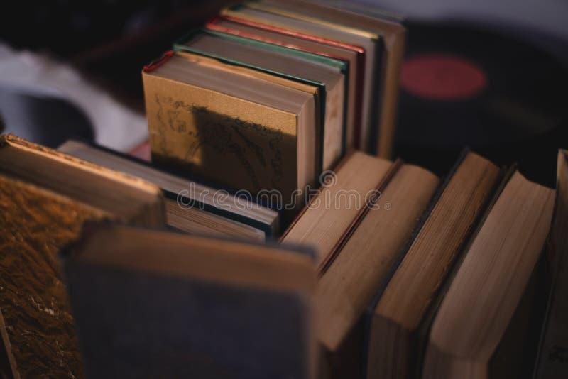 Εκλεκτής ποιότητας σωρός βιβλίων στην παλαιά ξύλινη επιφάνεια στο θερμό κατευθυντικό φως στοκ φωτογραφία με δικαίωμα ελεύθερης χρήσης