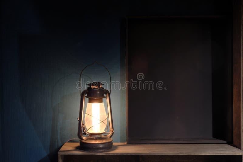 Εκλεκτής ποιότητας παλαιός λαμπτήρας κηροζίνης ενάντια σε έναν σκούρο μπλε τοίχο ράφια ξύλινα στοκ εικόνες