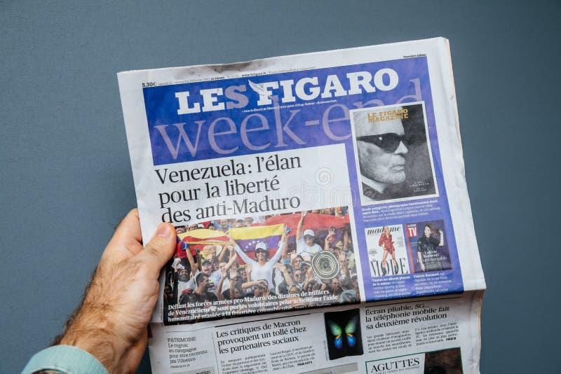 Εκμετάλλευση LE Φίγκαρο εφημερίδα ατόμων με τις παγκόσμιες ειδήσεις στοκ φωτογραφίες