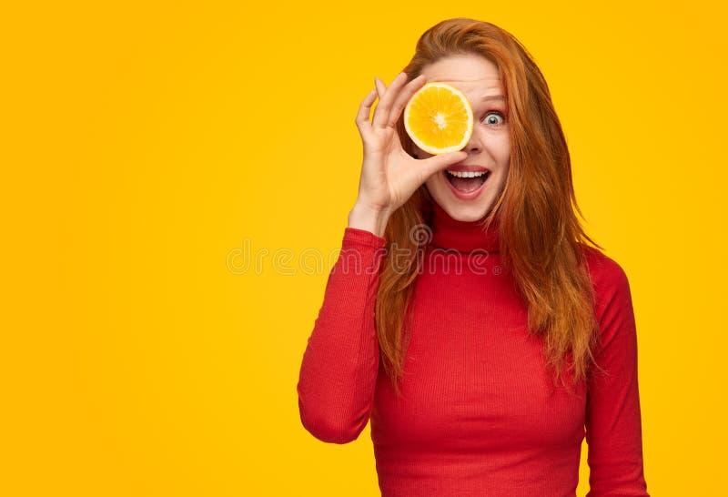 Εκφραστικό κορίτσι που καλύπτει το μάτι με την πορτοκαλιά φέτα στοκ φωτογραφία με δικαίωμα ελεύθερης χρήσης