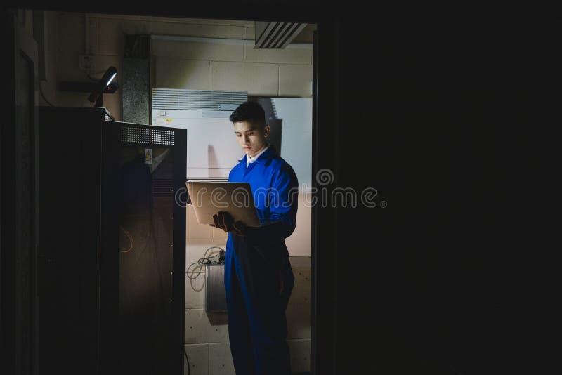 Εκπαιδευόμενος τεχνικός στο δωμάτιο κεντρικών υπολογιστών στοκ εικόνα