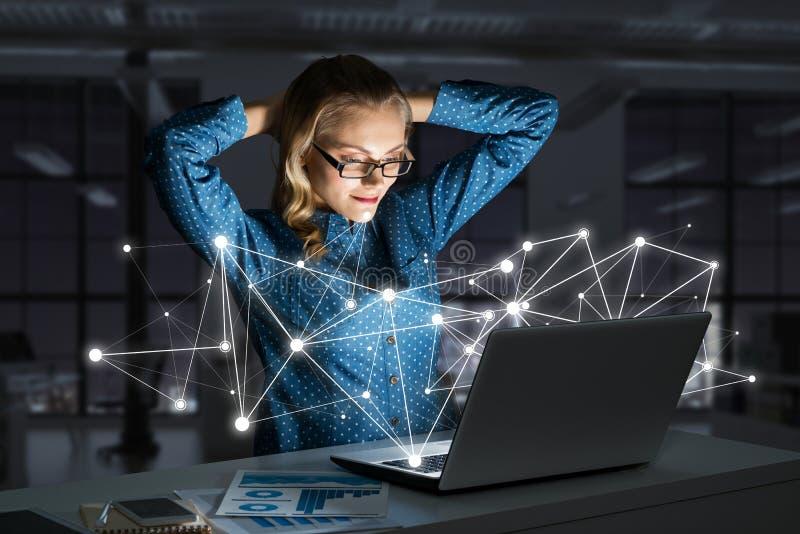 Ελκυστικά ξανθά φορώντας γυαλιά στο σκοτεινό γραφείο που χρησιμοποιεί το lap-top Μικτά μέσα στοκ εικόνες με δικαίωμα ελεύθερης χρήσης