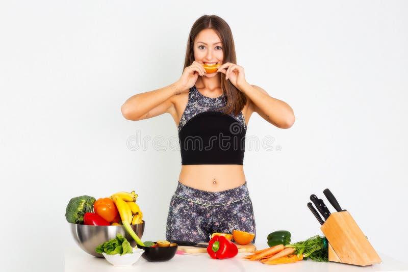 Ελκυστική γυναίκα ικανότητας, εκπαιδευμένη θηλυκή κατάλληλη αθλητική βέβαια νέα γυναίκα δύναμης bodybuilder που τρώει το πορτοκάλ στοκ εικόνα