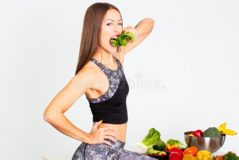 Ελκυστική γυναίκα ικανότητας, εκπαιδευμένη θηλυκή κατάλληλη αθλητική βέβαια νέα γυναίκα δύναμης bodybuilder που τρώει veg, οργανι στοκ εικόνες