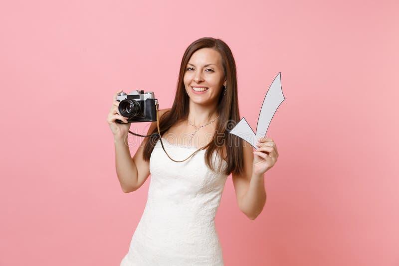 Ελκυστική γυναίκα νυφών στο γαμήλιο φόρεμα που κρατούν την αναδρομικά εκλεκτής ποιότητας κάμερα φωτογραφιών και το σημάδι ελέγχου στοκ φωτογραφία με δικαίωμα ελεύθερης χρήσης