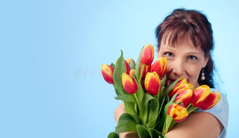Ελκυστική γυναίκα στο μπλε φόρεμα με μια ανθοδέσμη των κόκκινων και κίτρινων τουλιπών στοκ φωτογραφία