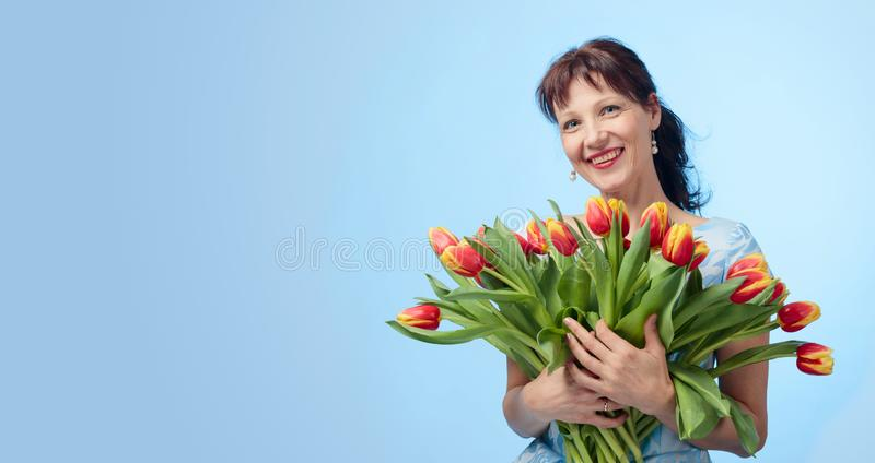 Ελκυστική γυναίκα στο μπλε φόρεμα με μια ανθοδέσμη των κόκκινων και κίτρινων τουλιπών στοκ φωτογραφία με δικαίωμα ελεύθερης χρήσης