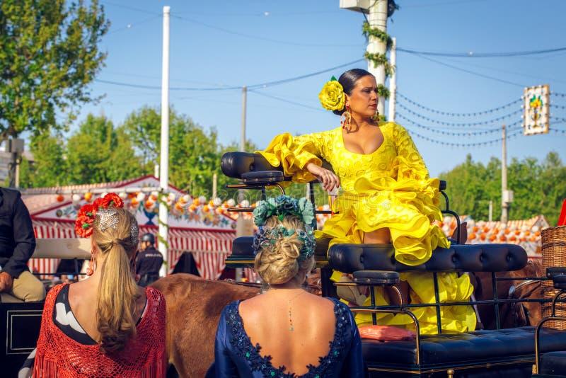 Ελκυστική γυναίκα στο παραδοσιακό φόρεμα που ταξιδεύει στις ένα συρμένες άλογο μεταφορές στην έκθεση Απριλίου, Σεβίλη δίκαιο Feri στοκ εικόνες