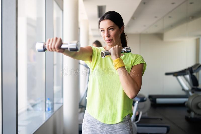 Ελκυστική νέα γυναίκα που επιλύει με τους αλτήρες σε μια γυμναστική στοκ εικόνες με δικαίωμα ελεύθερης χρήσης