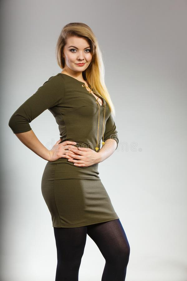 Ελκυστική ξανθή γυναίκα που φορά το σφιχτό πράσινο χακί φόρεμα στοκ φωτογραφία με δικαίωμα ελεύθερης χρήσης
