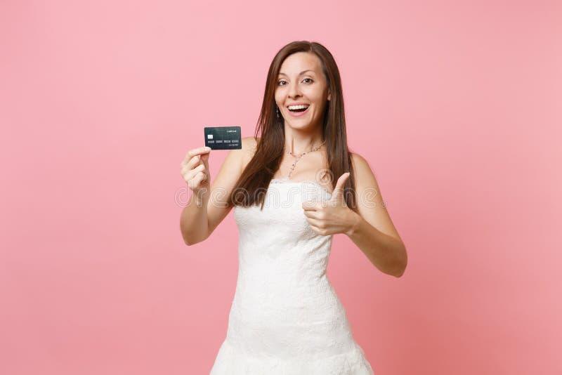 Ελκυστική χαρούμενη γυναίκα νυφών στην άσπρη πιστωτική κάρτα εκμετάλλευσης γαμήλιων φορεμάτων που παρουσιάζει αντίχειρα στη ρόδιν στοκ εικόνες