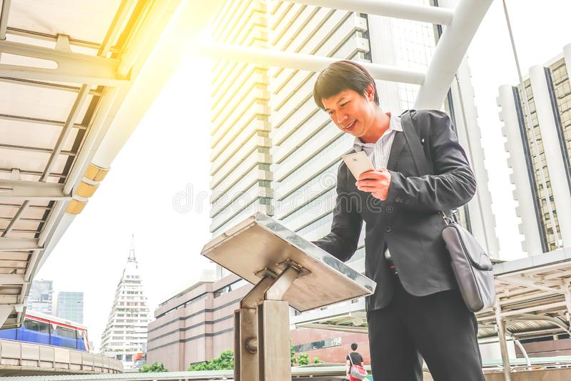 Ελκυστικός νεαρός άνδρας που στέκεται την μπροστινή μεγάλη ψηφιακή οθόνη με τα βασικά στοιχεία χαρτών πύργων με κινητό στοκ φωτογραφίες με δικαίωμα ελεύθερης χρήσης