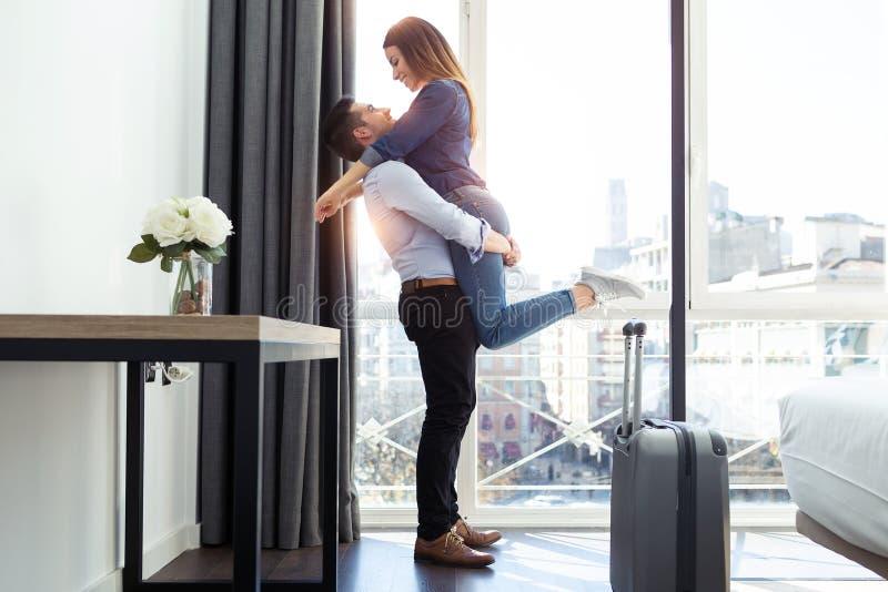 Ελκυστικό ευτυχές νέο ζεύγος ερωτευμένο έχοντας τη διασκέδαση και αγκαλιάζοντας στο δωμάτιο ξενοδοχείου στοκ εικόνες με δικαίωμα ελεύθερης χρήσης