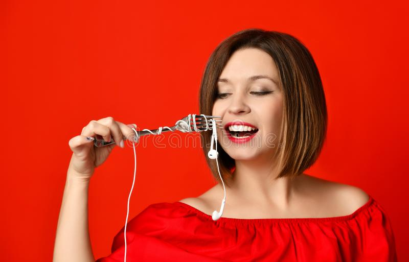 Ελκυστικό κορίτσι στο κόκκινο φόρεμα που κρατά ένα δίκρανο στα χέρια στο βούλωμα ακουστικών Προετοιμάστηκε να φάει στοκ φωτογραφία με δικαίωμα ελεύθερης χρήσης