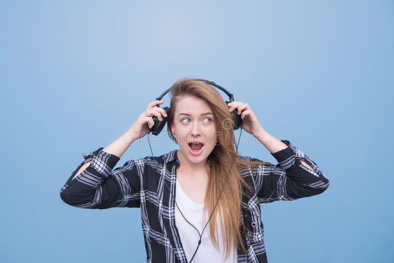 Ελκυστικό κορίτσι που τραβά τα ακουστικά στο κεφάλι της Το θετικό κορίτσι με τα ακουστικά σε ένα μπλε υπόβαθρο στοκ εικόνες
