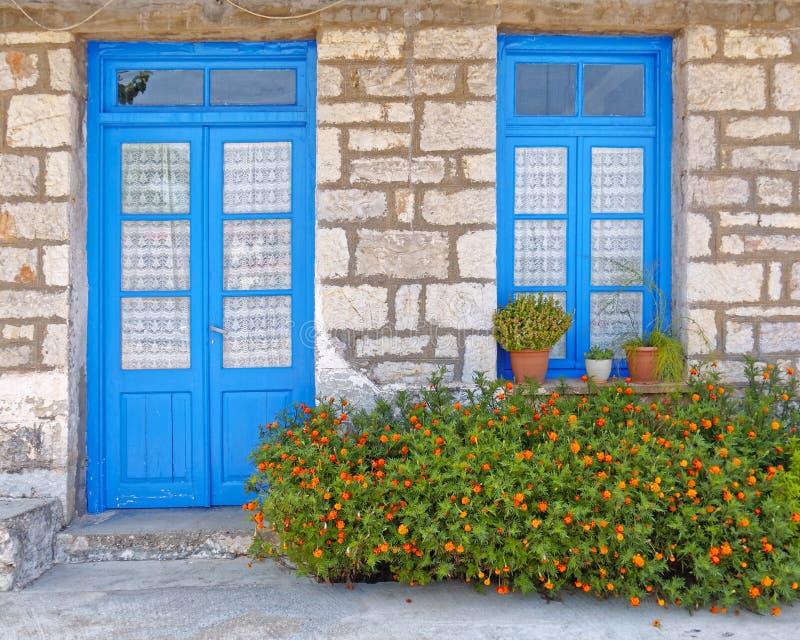 Ελλάδα, marigold λουλούδια μπροστά από την μπλε πόρτα και το παράθυρο, πρόσοψη σπιτιών στοκ φωτογραφία με δικαίωμα ελεύθερης χρήσης