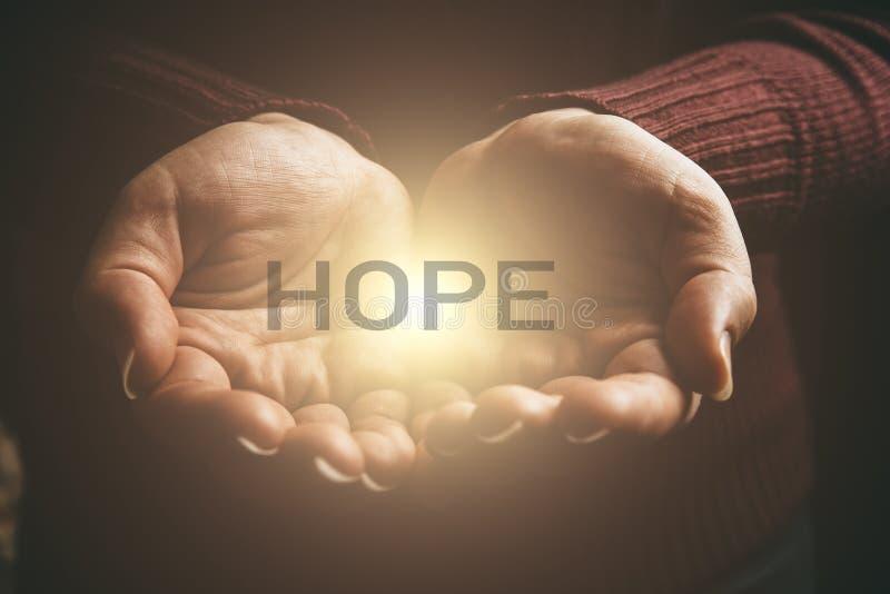 ΕΛΠΙΔΑ λέξης στο αφηρημένο φως στα θηλυκά χέρια, που προσφέρουν το σύμβολο βοήθειας, προστασίας και υποστήριξης Διανομή της ελπίδ στοκ φωτογραφία με δικαίωμα ελεύθερης χρήσης