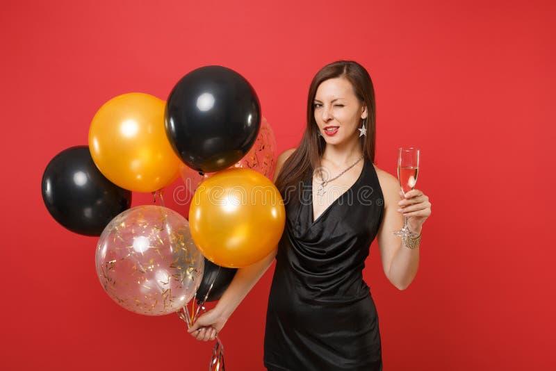 Εμπαθής γυναίκα στο μαύρο να αναβοσβήσει εορτασμού φορεμάτων γυαλί εκμετάλλευσης των μπαλονιών αέρα σαμπάνιας που απομονώνεται στ στοκ εικόνα με δικαίωμα ελεύθερης χρήσης
