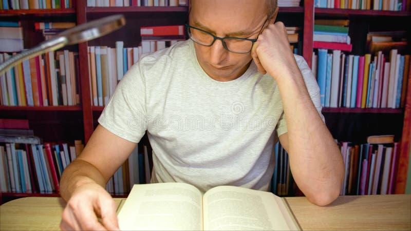 Ενήλικο βιβλίο ανάγνωσης ατόμων στον πίνακα με το λαμπτήρα στο υπόβαθρο ραφιών στο εγχώριο δωμάτιο στοκ φωτογραφία με δικαίωμα ελεύθερης χρήσης