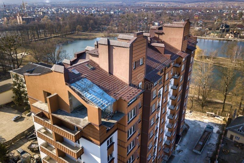 Εναέρια άποψη της νέας ψηλής πολυκατοικίας στην ήρεμη περιοχή στο υπόβαθρο της ανάπτυξης του τοπίου πόλεων κάτω από το φωτεινό μπ στοκ εικόνες με δικαίωμα ελεύθερης χρήσης