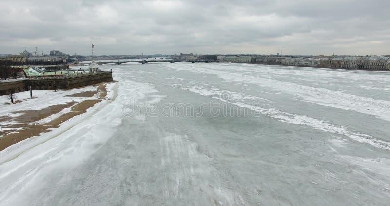 εναέρια όψη Πέταγμα κατά μήκος του ποταμού Neva στο χειμερινό συννεφιάζω κρύο καιρό Γέφυρα πέρα από τον ποταμό Πετρούπολη στο σού στοκ εικόνα