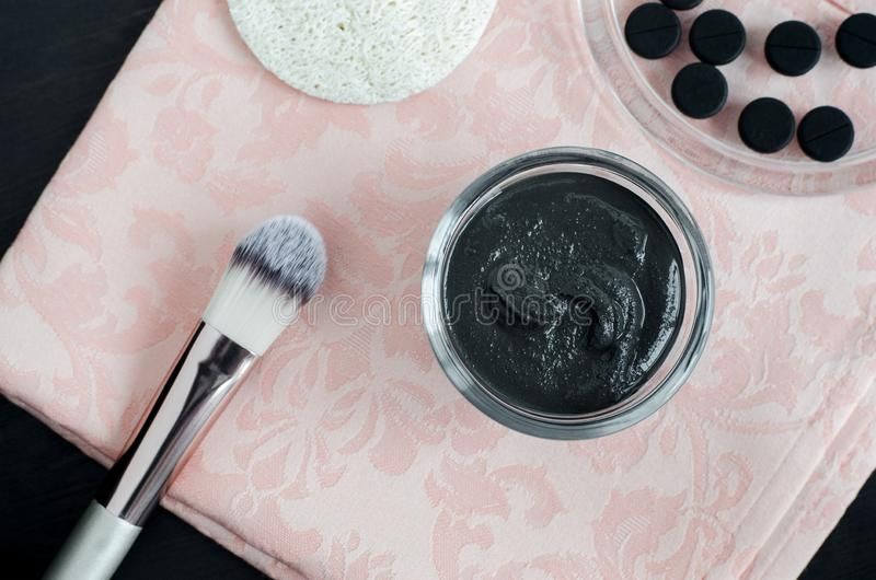 Ενεργοποιημένες DIY πρόσωπο ξυλάνθρακα/μάσκα τρίχας στο μικρό κύπελλο γυαλιού Σπιτική επεξεργασία ομορφιάς Τοπ όψη στοκ φωτογραφίες