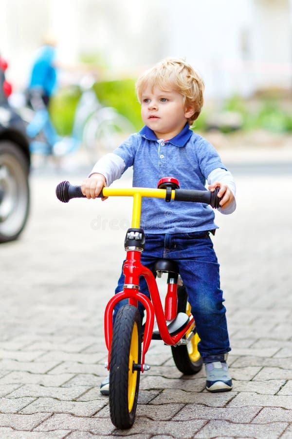Ενεργό ξανθό αγόρι παιδιών στα ζωηρόχρωμα ενδύματα που οδηγούν την ισορροπία και το ποδήλατο του αρχαρίου ή ποδήλατο στον εσωτερι στοκ φωτογραφία με δικαίωμα ελεύθερης χρήσης