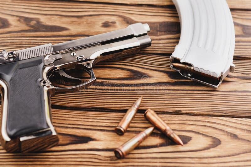 Ενιαίο στιλπνό πιστόλι μετάλλων και ασημένιο περιοδικό με τις διεσπαρμένες σφαίρες για το επιθετικό τουφέκι στοκ εικόνα