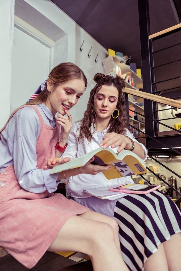 Ενδιαφερόμενα κορίτσια που μελετούν μαζί στον καφέ που χρησιμοποιεί τα εγχειρίδια στοκ εικόνες με δικαίωμα ελεύθερης χρήσης