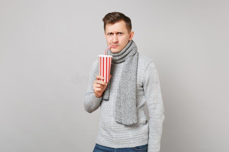 Ενδιαφερόμενος νεαρός άνδρας στην γκρίζα κόλα κατανάλωσης μαντίλι πουλόβερ ή σόδα από το πλαστικό φλυτζάνι που απομονώνεται στο γ στοκ εικόνα με δικαίωμα ελεύθερης χρήσης