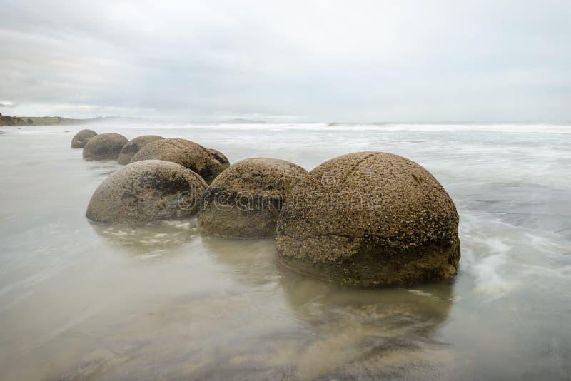 Εντυπωσιακοί λίθοι Moeraki και τα κύματα Ειρηνικών Ωκεανών στοκ φωτογραφίες