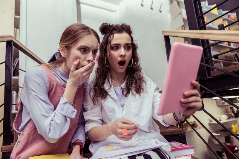 Εντυπωσιασμένα κορίτσια που τρομοκρατούνται με το περιεχόμενο στην ταμπλέτα στοκ φωτογραφία