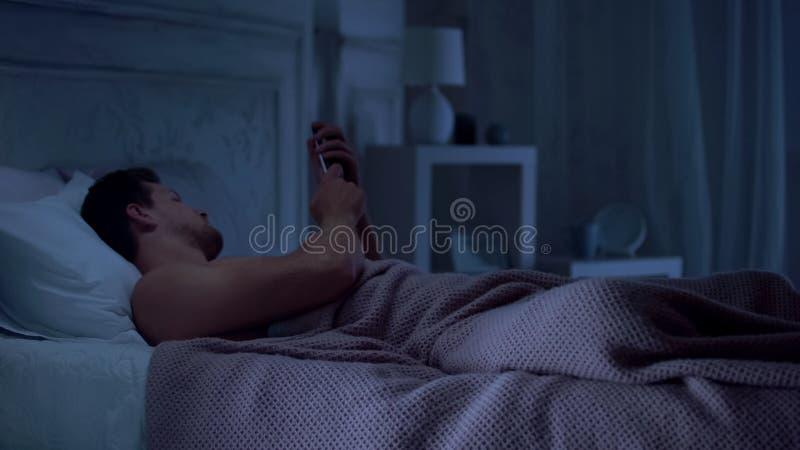Εξαρτημένος κινητών τηλεφώνων που βρίσκεται στο κρεβάτι και που κουβεντιάζει στο smartphone αντί του ύπνου στοκ φωτογραφία