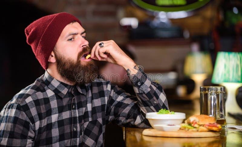 Εξαπατήστε το γεύμα Υψηλά τρόφιμα θερμίδας Εύγευστη burger έννοια Απολαύστε το γούστο φρέσκο burger Το πεινασμένο άτομο Hipster τ στοκ εικόνες