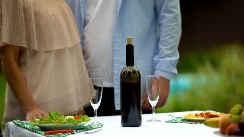 Εξυπηρετώντας πίνακας ζεύγους πριν από την ημερομηνία στο εξοχικό σπίτι, σπιτικές παραδόσεις κρασιού στοκ εικόνες