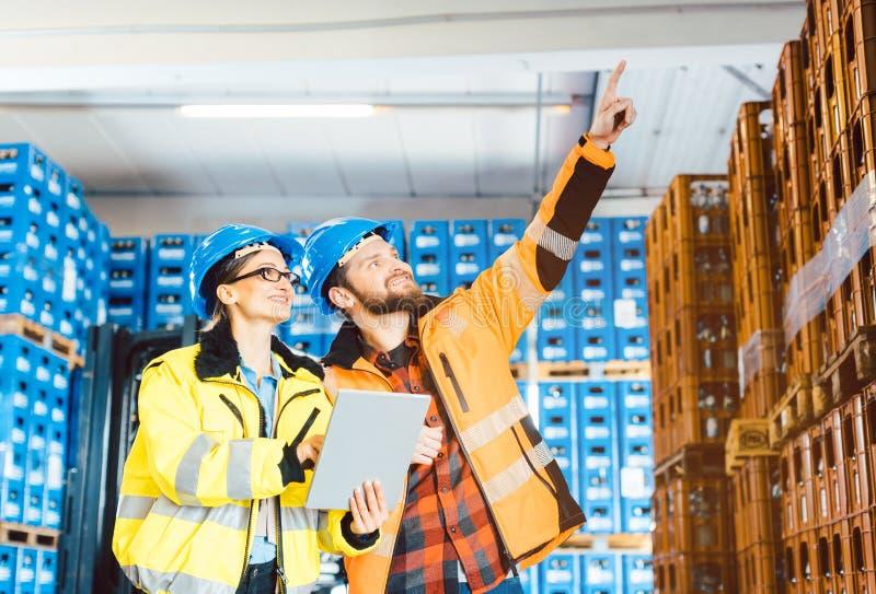 Εργαζόμενοι σε μια αποθήκη εμπορευμάτων διοικητικών μεριμνών που προγραμματίζει το επόμενο πρόγραμμα στοκ εικόνα με δικαίωμα ελεύθερης χρήσης