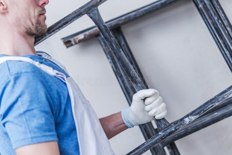 Εργαζόμενος με τα υλικά σκαλωσιάς στοκ φωτογραφία με δικαίωμα ελεύθερης χρήσης