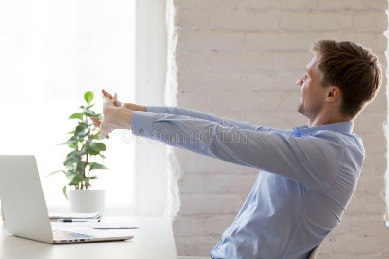 Εργαζόμενος που κάνει τις αποτελεσματικές τεντώνοντας ασκήσεις κατά τη διάρκεια της εργάσιμης ημέρας στοκ φωτογραφία